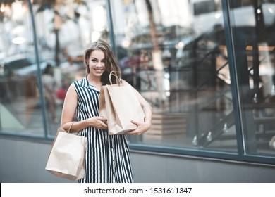 Smiling girl 20-24 year old holding paper bags walking over shopwindow on street closeup. Looking at camera. Black friday sales.