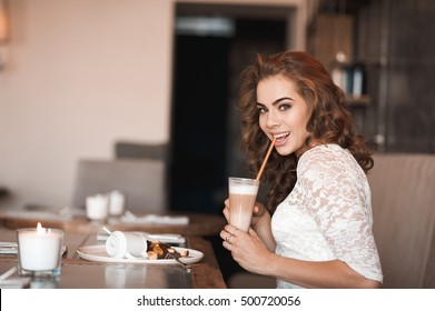 Smiling girl 20-24 year old drinking coffee and eating cake in cafe. Looking at camera.