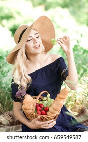 Smiling girl 24-29 year old having picnic in park. Holding wicker basket with fruits and bread. Wearing straw hat and stylish blue dress outdoors. Summer time. 20s.