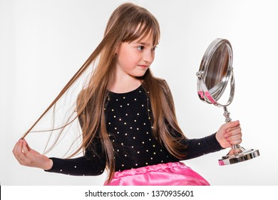 A smiling girl of about nine with long hair attentively examines herself in the mirror