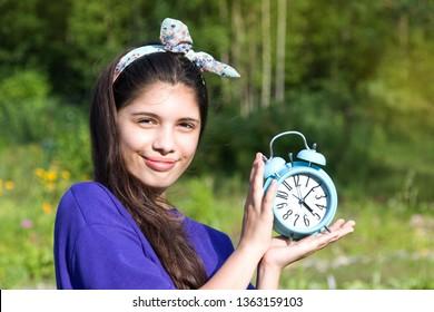 Smiling girl with alarm clock in summer garden