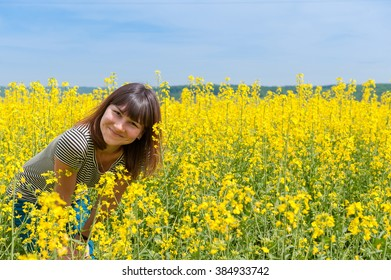 smiling girl among a field of yellow flowers
