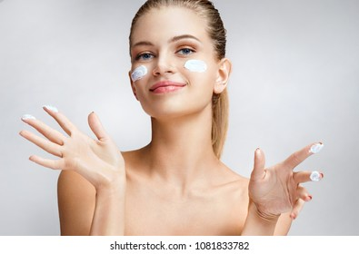 Smiling girl applying moisturizing cream on her face. Photo of young girl with flawless skin on grey background. Skin care and beauty concept