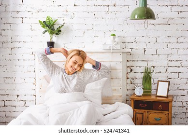 Smiling girl awakes in bedroom