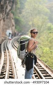 Smiling girl backpacker on the railway background