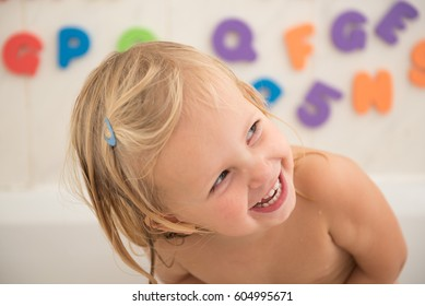 Smiling  girl in bathroom with colorful foam letters and numbers in background.Water fun for kids.