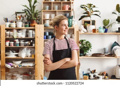 Smiling girl in black apron and T-shirt happily looking aside with handmade dishes on shelves on background at pottery studio