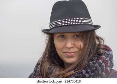 Smiling girl with a black hat and a big scarf