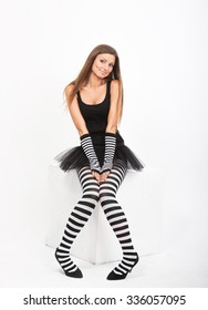 Smiling girl in black and white striped tights sitting on a white cube