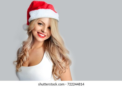 Smiling girl blonde with red lipstick and in santa claus hat