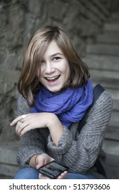 smiling girl in a blue scarf sitting on stone stairs outdoors