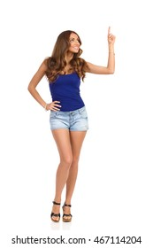 Smiling girl in blue shirt, jeans shorts and cork heels standing with hand on hip pointing up and looking. Full length studio shot isolated on white.