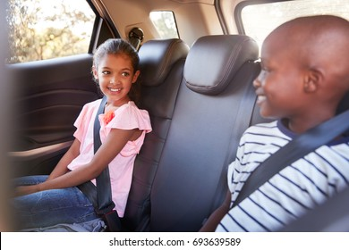 Smiling girl and boy looking at each other in car on a trip