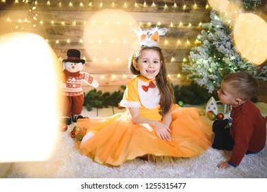 smiling girl and boy looking at herin christmas lights