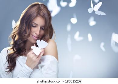 Smiling girl with butterflies in studio