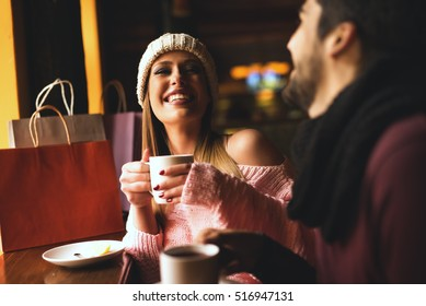 Smiling girl in a cafe drinking tea with your boyfriend.