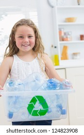 Smiling girl carrying recycling box of the plastics bottles