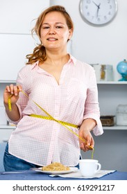 Smiling girl checks her waist with measuring tape for control volume with grain diet food