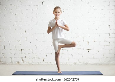 Smiling girl child practicing yoga, standing in Vrksasana exercise with namaste, Tree pose, working out wearing sportswear, t-shirt, pants, indoor full length, white loft studio background