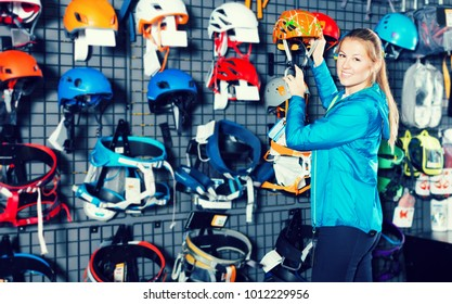 Smiling girl chooses reliable helmet at sports store