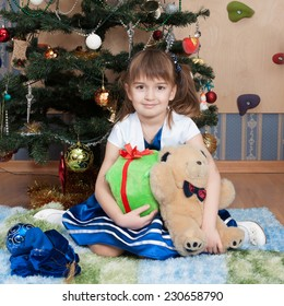 Smiling girl with Christmas gifts at Christmas tree (6 years)