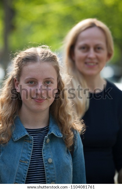 Smiling girl in a close-up, mother in a background also happy