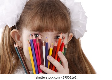 A smiling girl with color pencils in hands on a white background. Schoolgirl is holding coloured pencils.