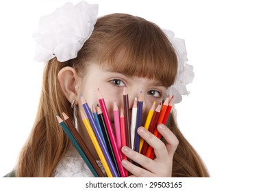 A smiling girl with color pencils in hands on a white background Schoolgirl is holding coloured pencils.