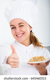 smiling girl cook with chestnut hair shows plate of porrige