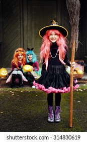 Smiling girl in costume of Halloween witch looking at camera with her friends on background