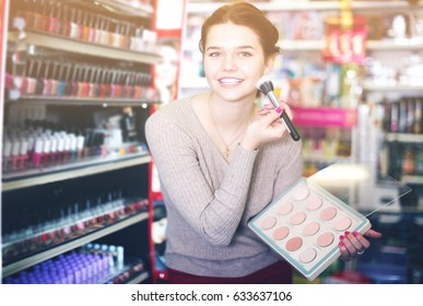 Smiling girl customer looking for bright pillow in home textile shop