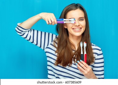 Smiling girl with dental braces holding toothy brush. Blue wall back.
