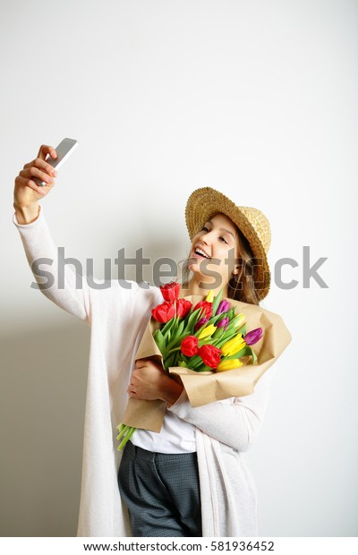 Smiling girl doing selfie with a bouquet of tulips in hand