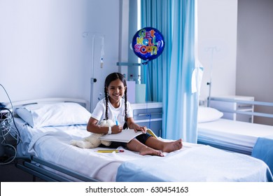 Smiling girl drawing picture in a book while sitting on hospital bed