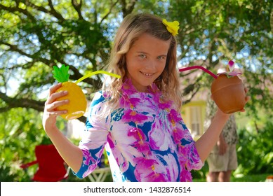 Smiling girl dressed up for a Hawaiian luau, wearing a flower dress and holding tropical drinks