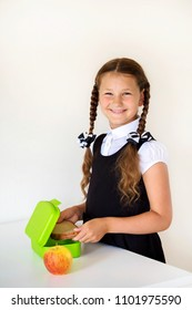 Smiling girl dressed in school uniform collects lunch for school in the kitchen. Child puts sandwich in the lunchbox. Next to the lunchbox is an apple. Kid himself prepares for school. Back to school.