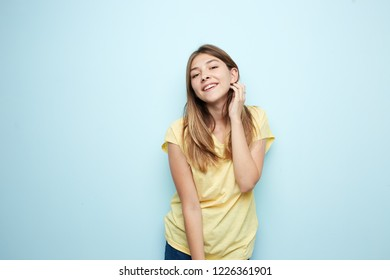 Smiling girl dressed in a yellow t-shirt and jeans is on a blue background in the studio