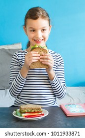 Smiling girl eat healthy sandwich with salad, avocado and other vegetables