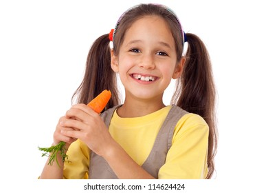 Smiling girl eating the carrot, isolated on white