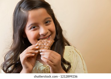 Smiling girl eating a chocolate bar with both hands