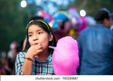 Smiling girl eating a cotton Candy at fair.
