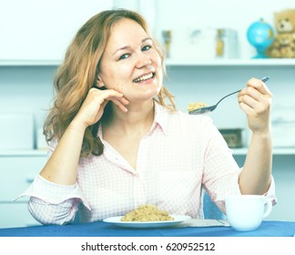 Smiling girl eating dietary oat cereal gruel for health and wellness