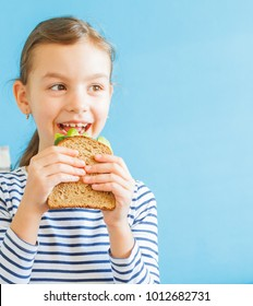 Souriante fille mangeant un sandwich sain avec de la salade et des avocats