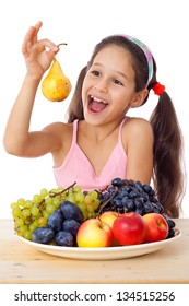 Smiling girl eating a pear on the desk with plate of fruits, isolated on white
