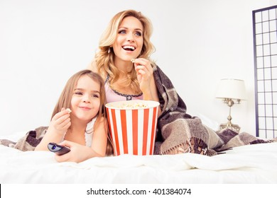 Smiling girl eating popcorn and watching cartoons with her mother