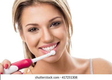 Smiling girl with electric toothbrush, brushing teeth