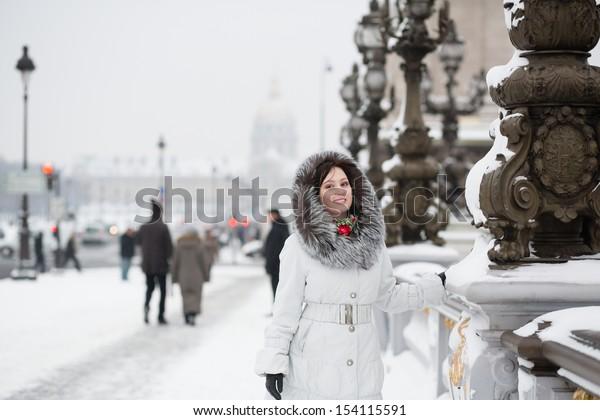 Smiling girl enjoying rare snowy day in Paris