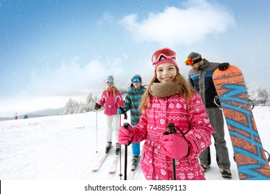 Smiling girl with family on ski terrain ready for skiing
