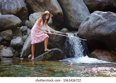 Smiling girl fishing in a mountain stream. Fun and relax