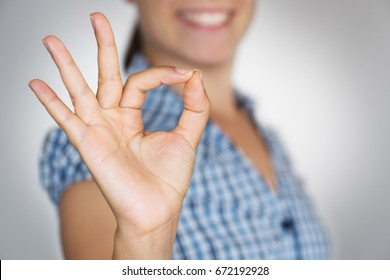 Smiling girl gesturing OK sign with her hand